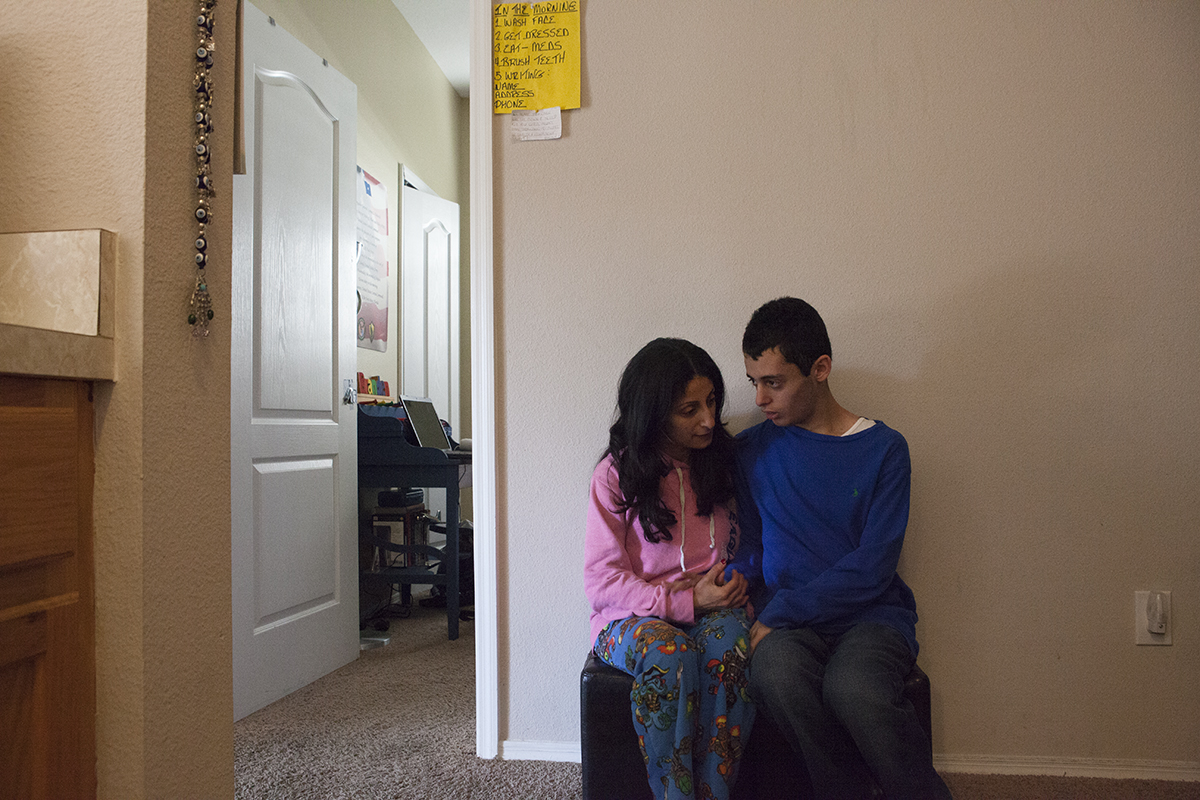 Renee with her son Branden sitting together in the early morning, outside his bedroom, talking about the day ahead.Tampa, FL.