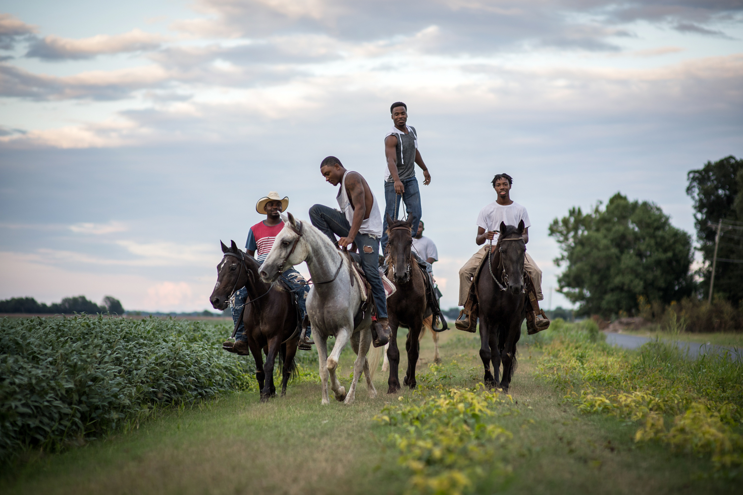 A group of young cowboys ride at dusk near the city limits of Cleveland, Mississippi.