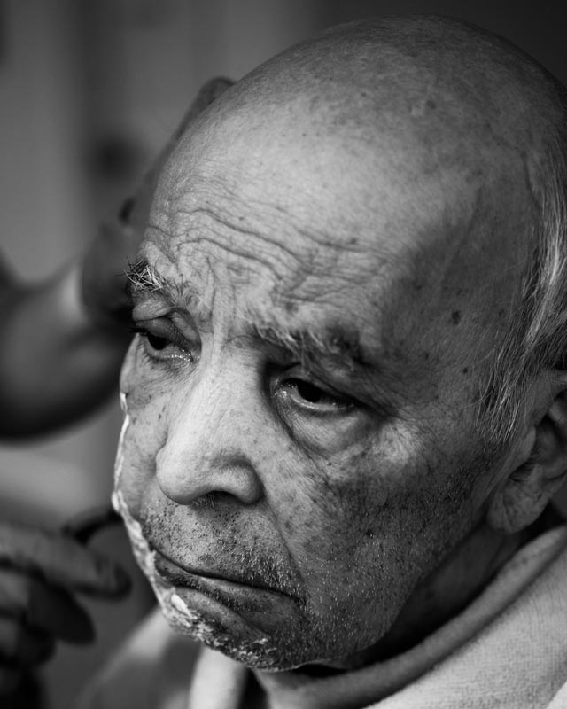 The nurse aide shaves Abuelo on a Monday afternoon.