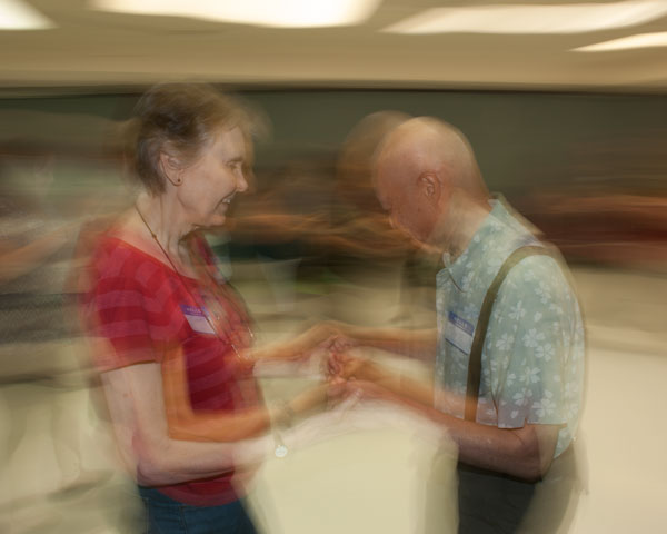 Two attendees to the Easing Memory Loss event at the Davis Senior Center on June 23, 2017, practice dance steps taught by Barbara Nicholas.