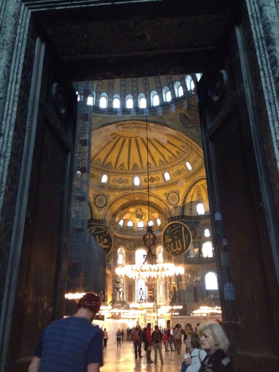 "Stepping into the Hagia Sofia. Note the huge gold mosaic of the Virgin Mary holding baby Jesus in the dome at the front and the two huge Islamic ""billboards"" to either side. Crazy experience."