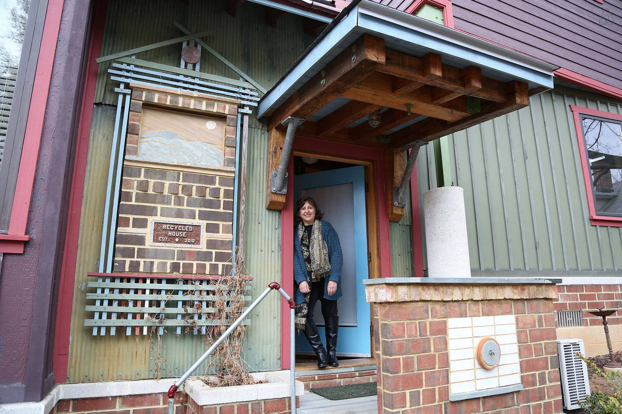 Debra proudly welcomes every visitor to the Recycled House