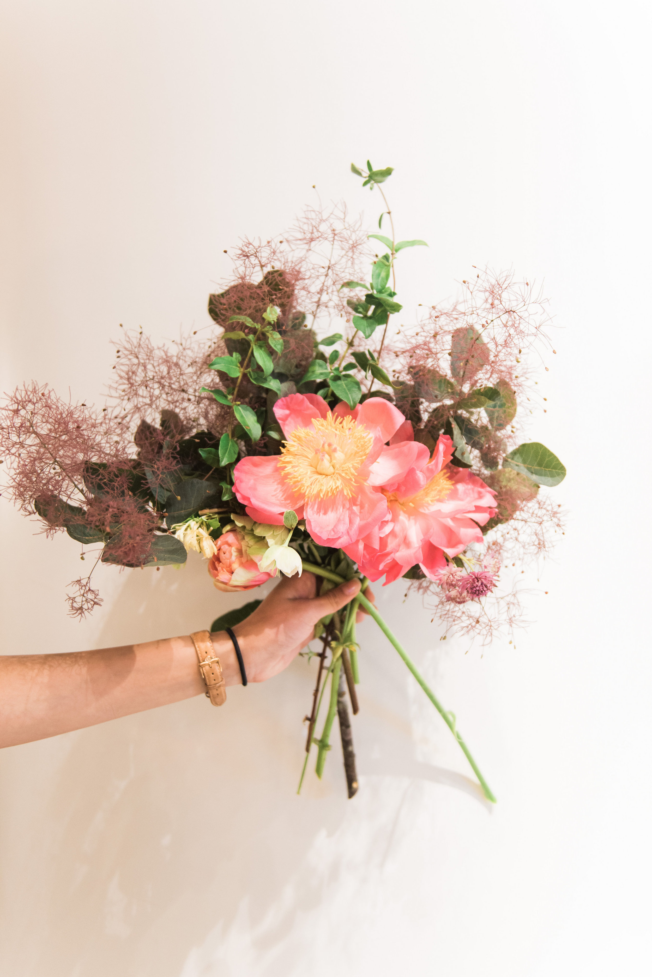Our floral recipe - 1 to 3 coral charm peonies depending on the size of your vessel3 stems of peach ranunculus3 stems of fritillaria2 stems of green hellebores2 pink french tulips2 stems of mauve astrantia2 stems of mauve lisianthusforaged smokebush, nandina, oak, and eleagnus