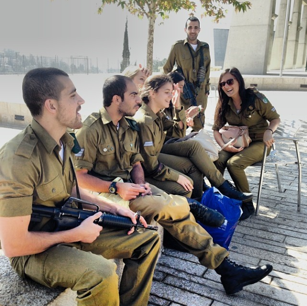 Israeli military hanging out with a machine gun in a public square in Jerusalem.