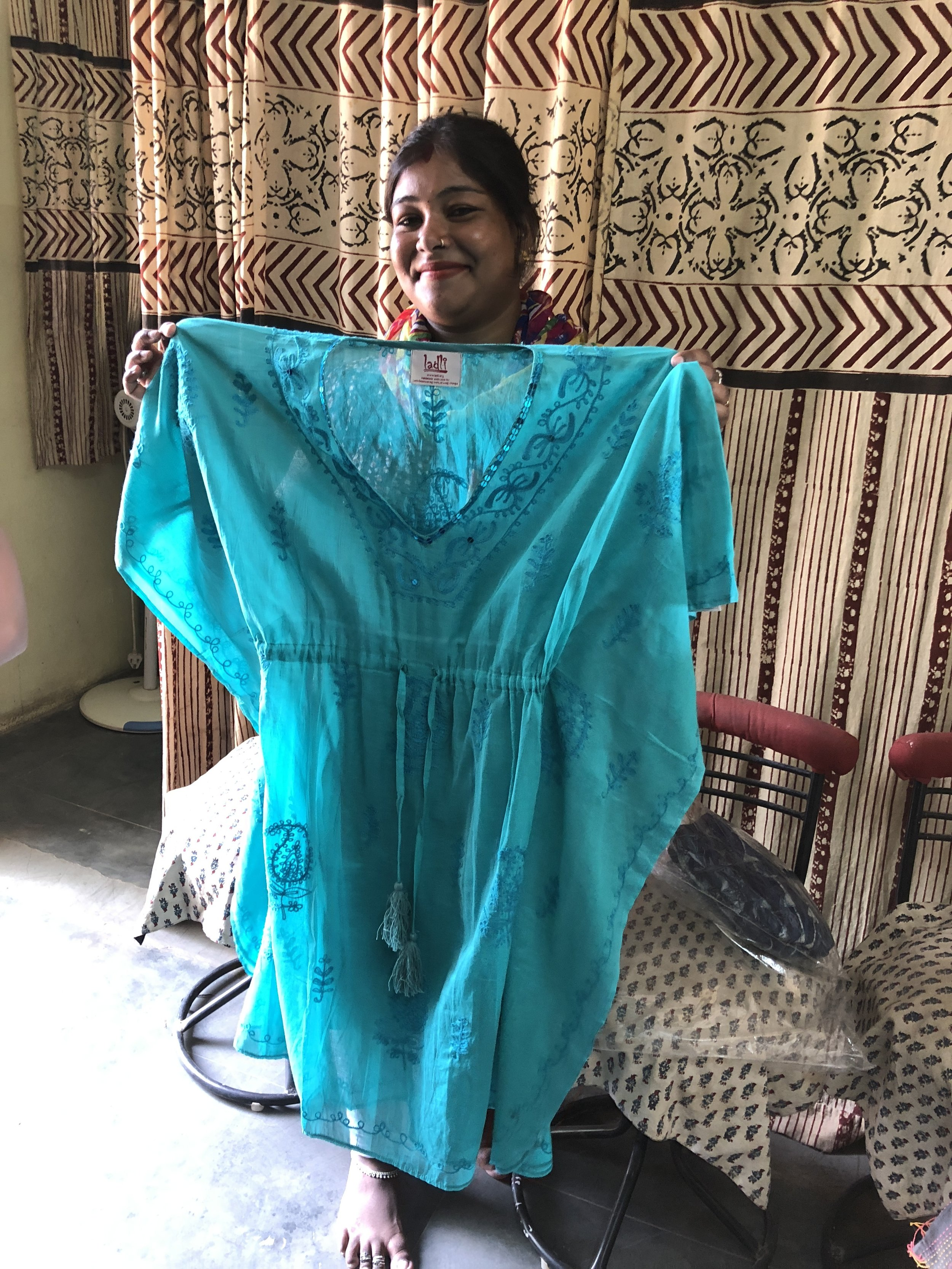 Tulsi holds up a hand embroidered kaftan made by the boys of  Ladli . They are in another building that we didn't have the time to visit.