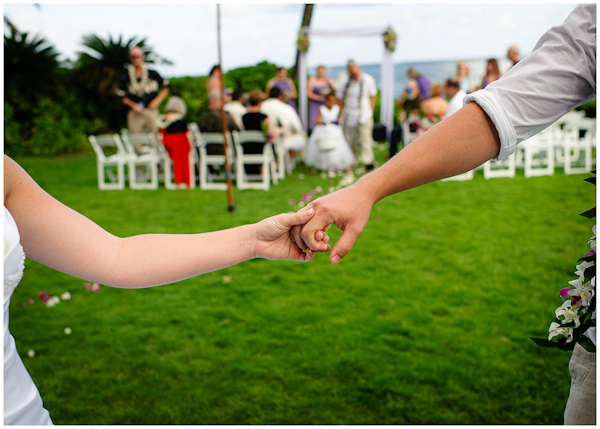 bride and groom holding hands down wedding aisle exit