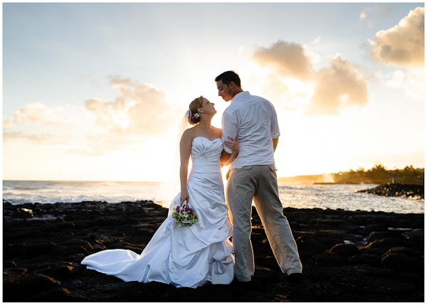 bride and groom in front of sunset on kauai