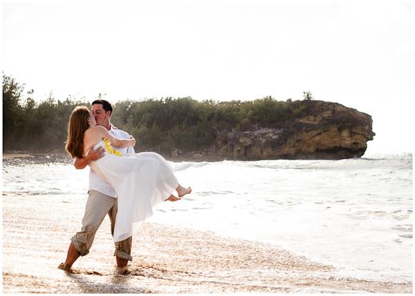 groom carrying bride on shipwreck beach hawaii