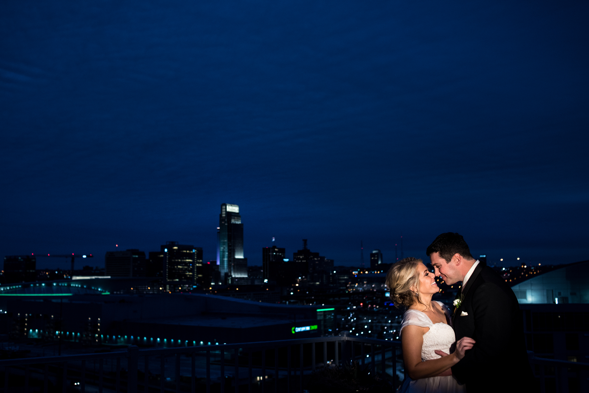 Sara and Tom making winter nosies on a top secret rooftop overlooking Omaha's skyline.
