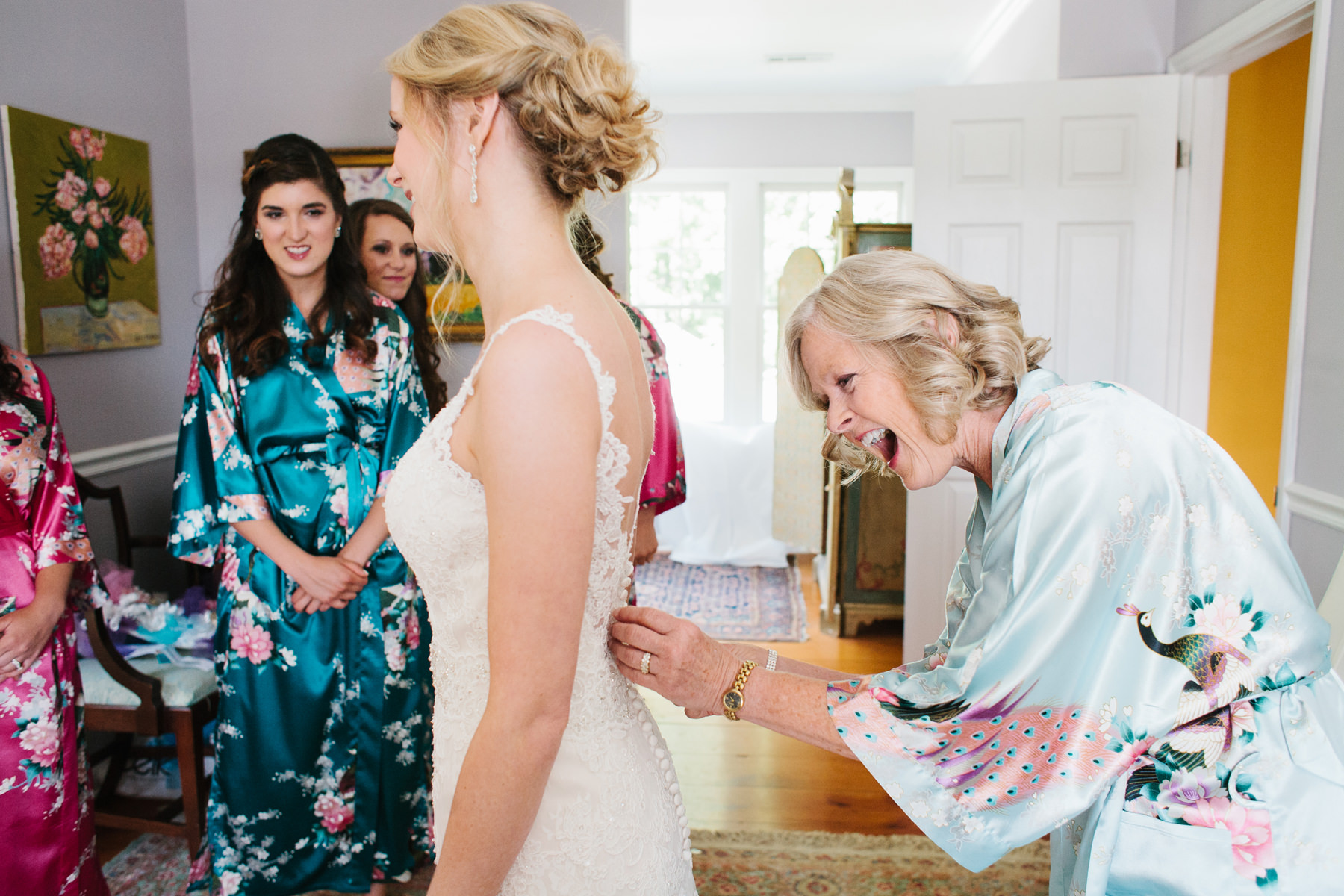 Bride Putting on Dress with Mom