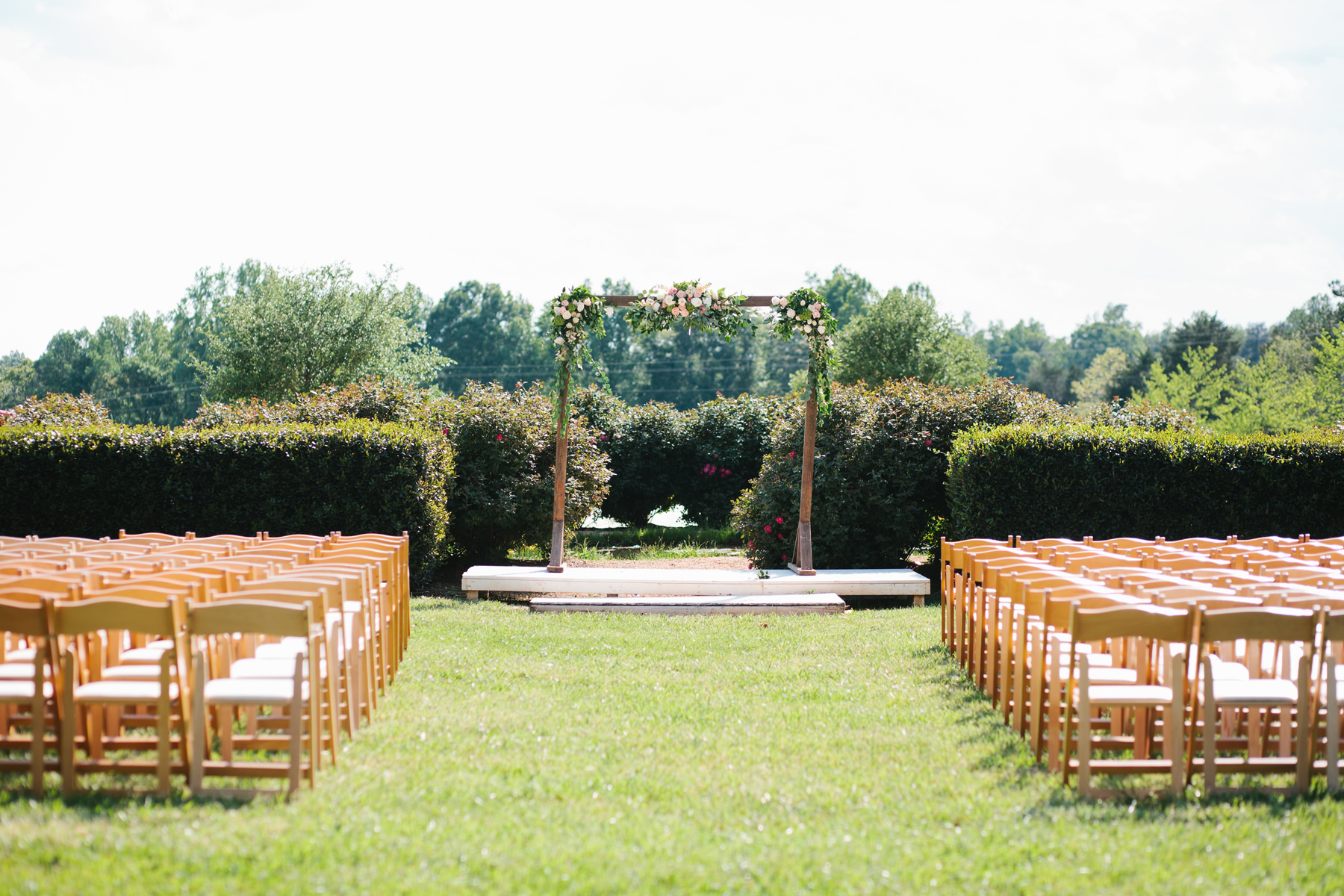 Outdoor Ceremony Decor with Floral Arch and Chairs