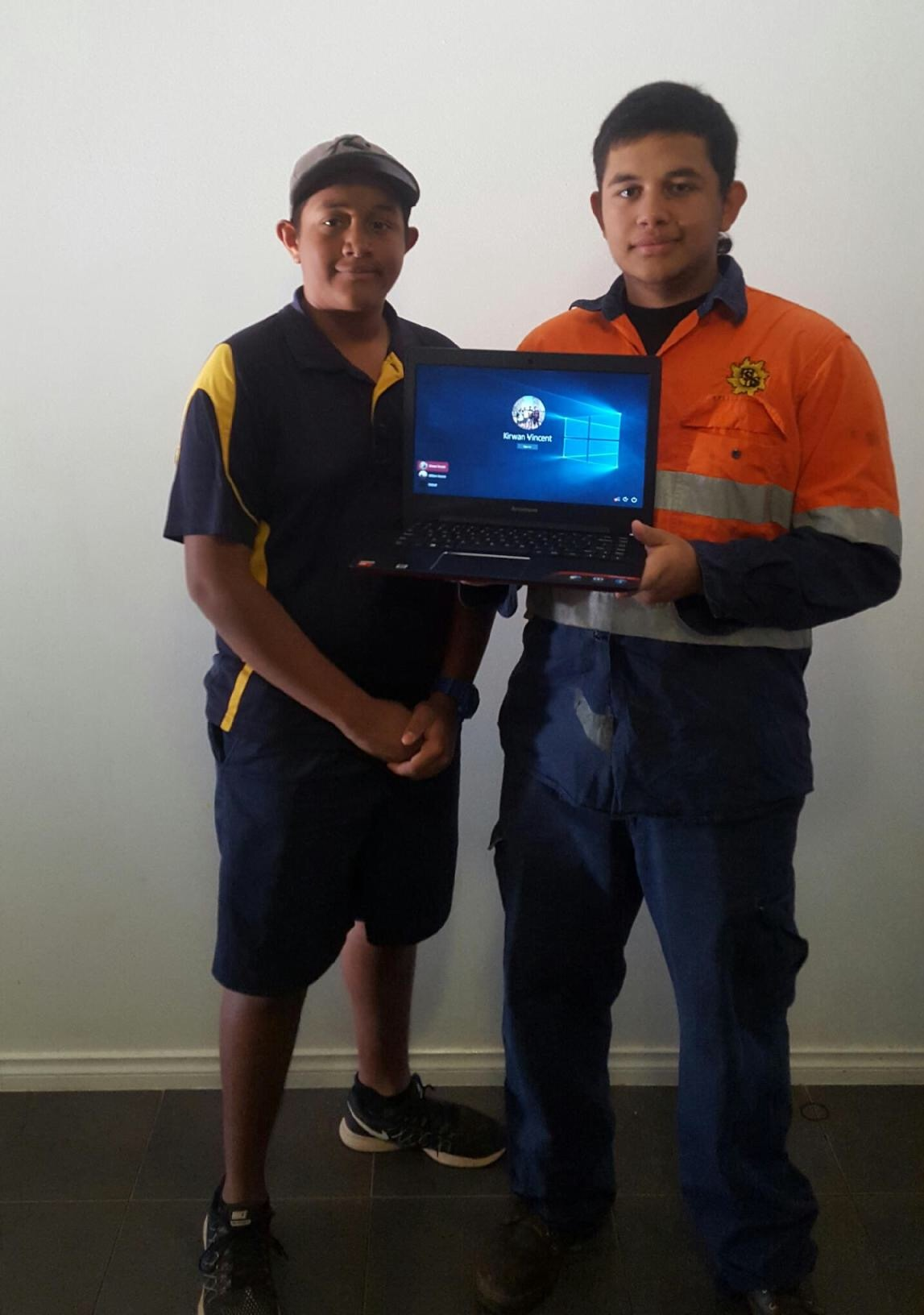 William and Kirwan Vincent with the laptop from the scholarship received from KRED Enterprises.