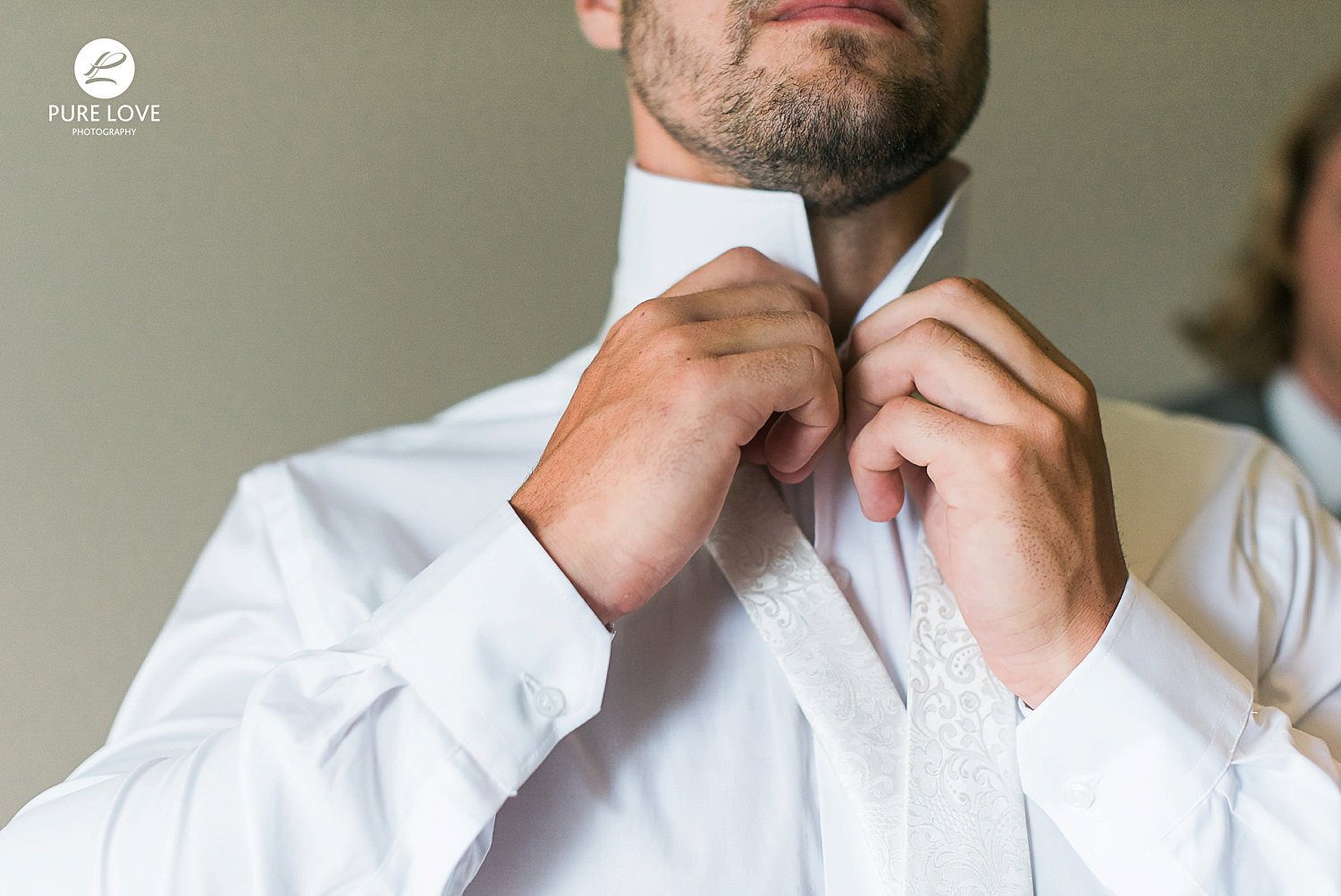 grrom getting ready, groom buttoning his shirt