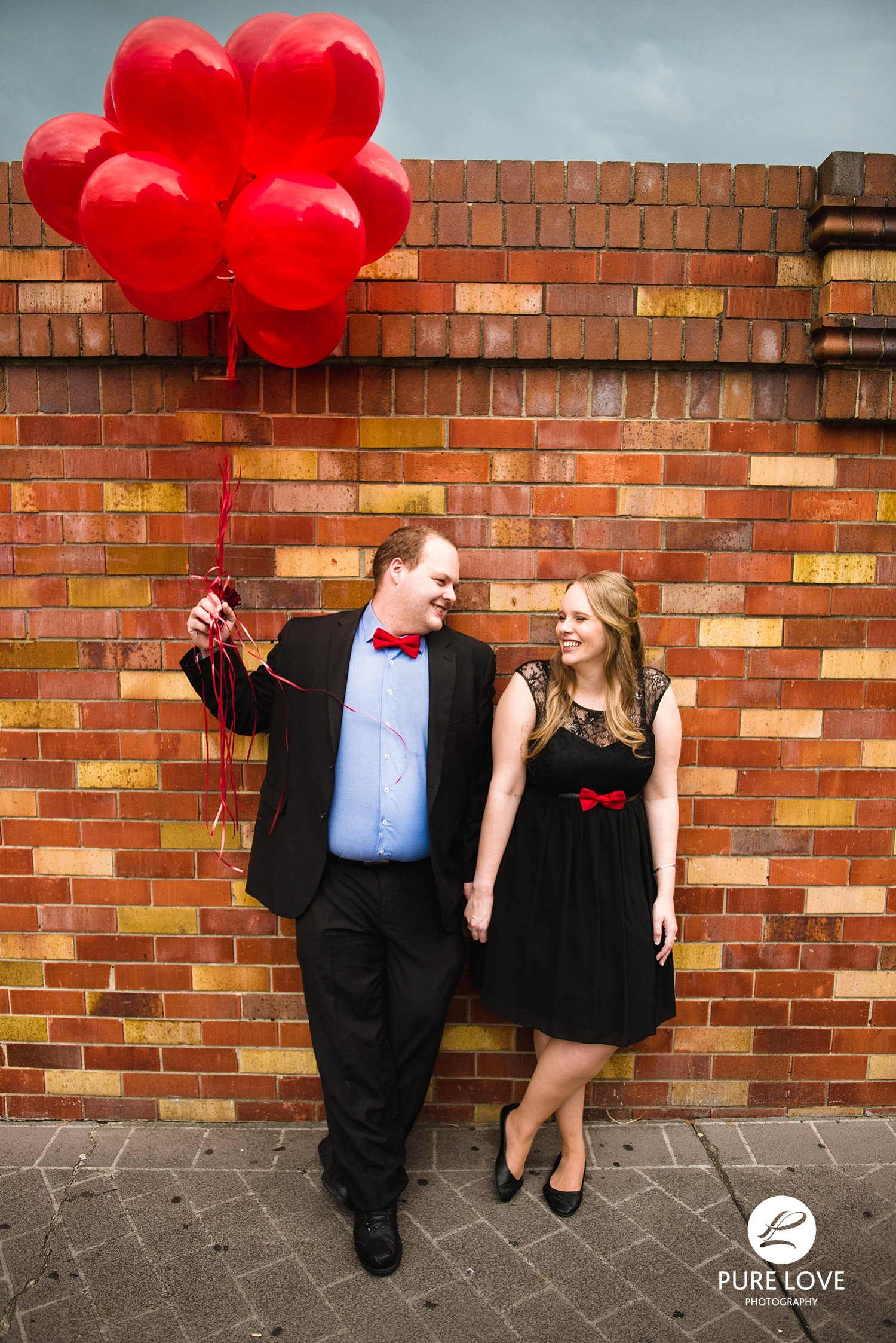 So much fun at Engagement Session. With red balloons at brick wall