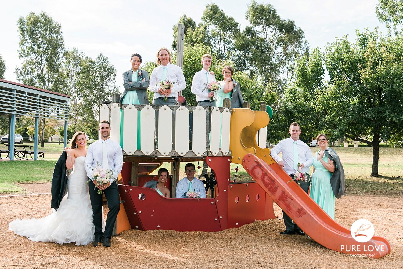 bridal party on playground. fun wedding photos