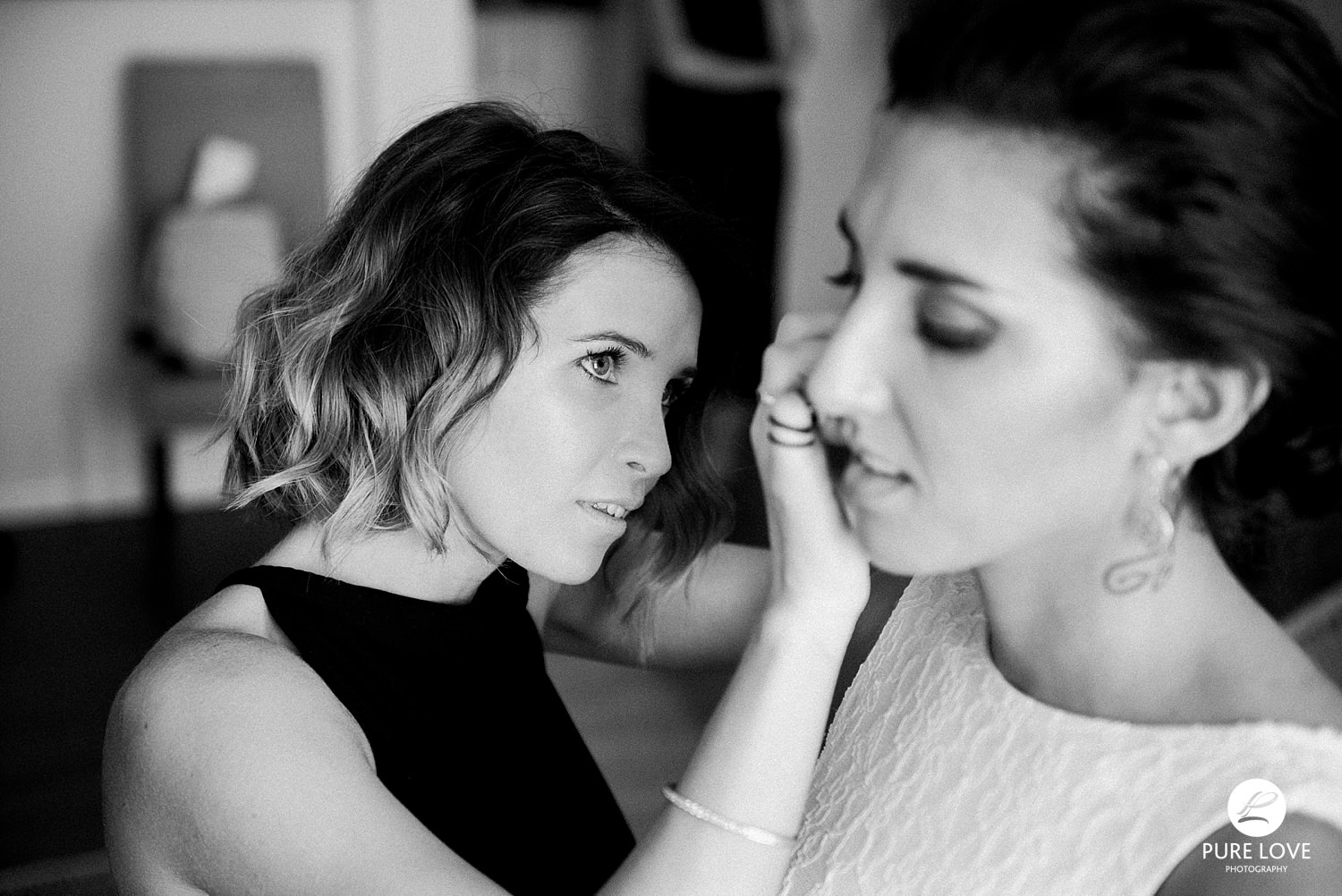 bridesmaid putting earrings on the bride. wedding preparation moments