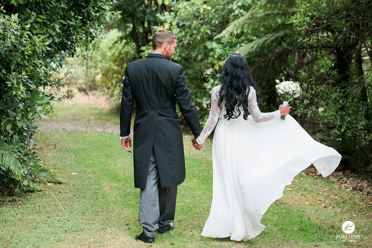 bride and groom walking away together flying dress