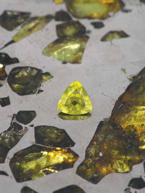 This picture shows a 1.12 carat peridot taken from the Esquel meteorite sat on a polished slice of it