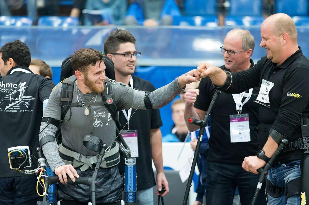 IHMC Pilot Mark Daniel and Cybathlon champion Van Reuschen. Tyson Cobb looks on. Credit: ETH Zürich/Alessandro Della Bella