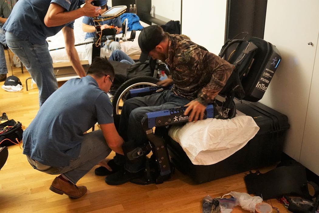 During a practice session prior to Cybathlon, Tyson Cobb straps Mark Daniel into the exo. Credit: Brian Blickenstaff
