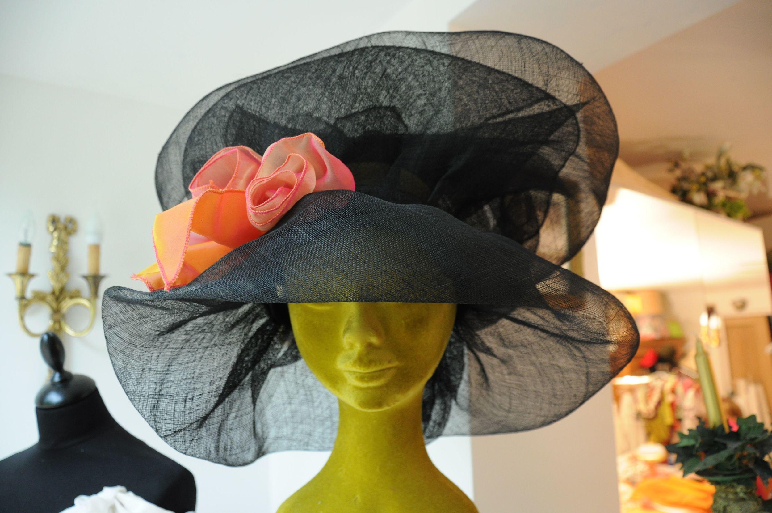 Chapeau en sisal noir avec décorations de fleurs en mousseline de soie orangées sur mesure assorti à la tenue