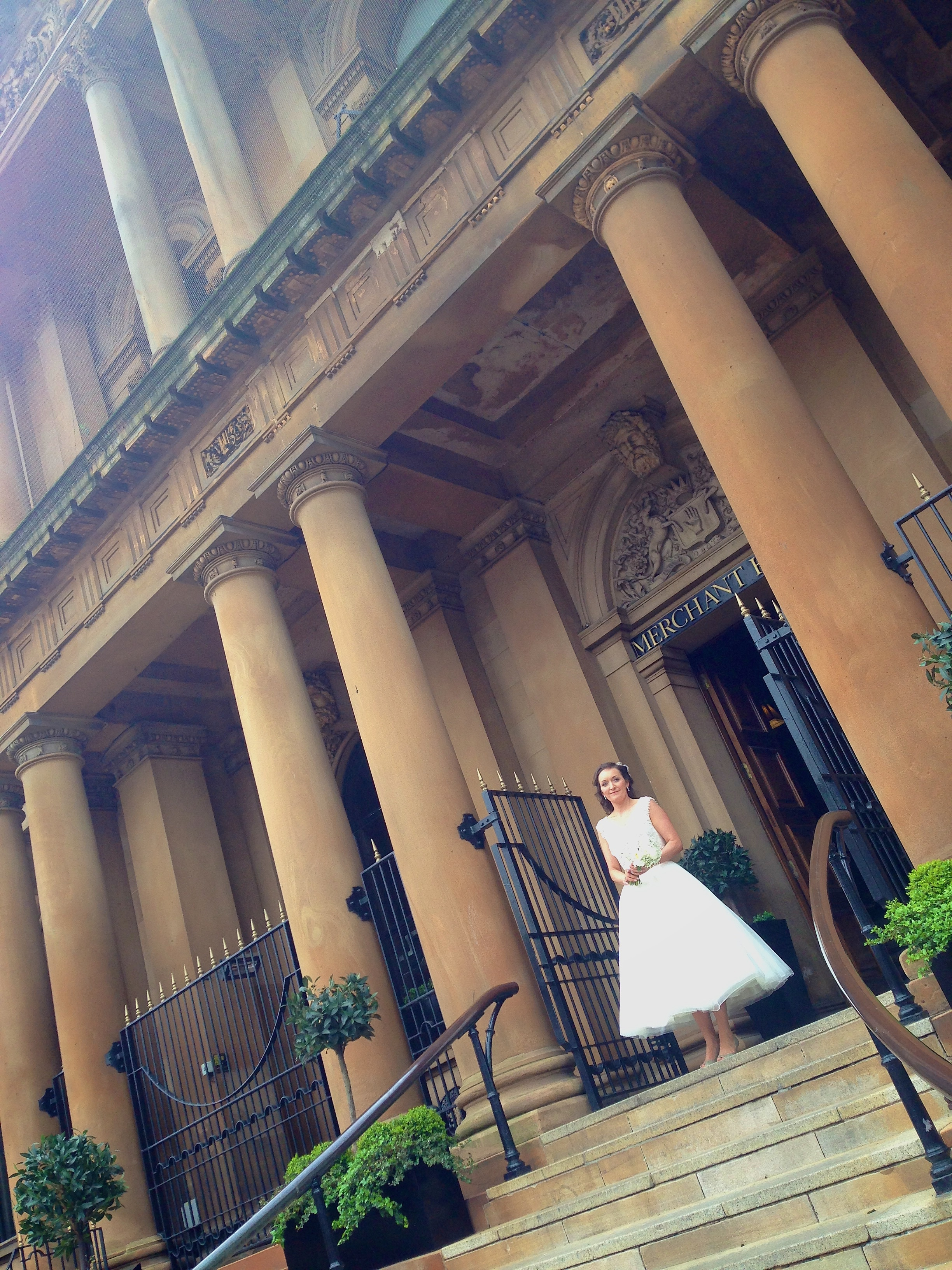 The Bride on the steps of the Merchant Hotel, Belfast. ©  Wedding Photography by Vivid Confetti