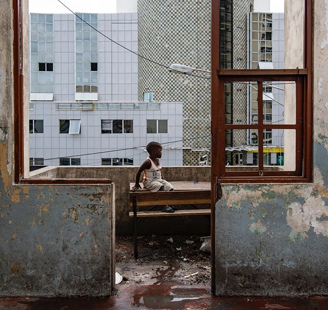 A child looks out at city streets from the balcony of a damaged school turned shelter for over 3,000 people in the afternoon of cyclone idai. #mozambique #beira #nikon #cycloneidai #climatechange #urban #urbanlandscape #africa