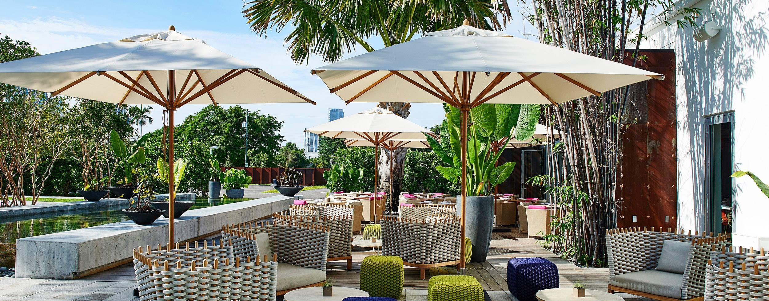 The 10' Square Levante Commercial Market Umbrella enhances the decor of this Miami hot spot.