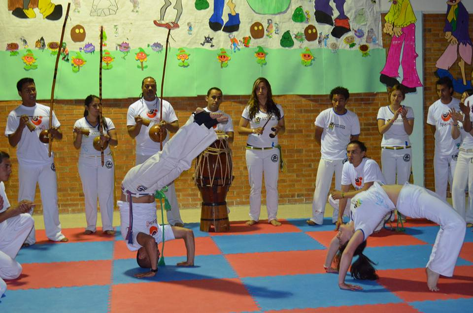 Our project leader and Capoeira trainer Cristhian Casallas plays with one of the students before giving her the new belt