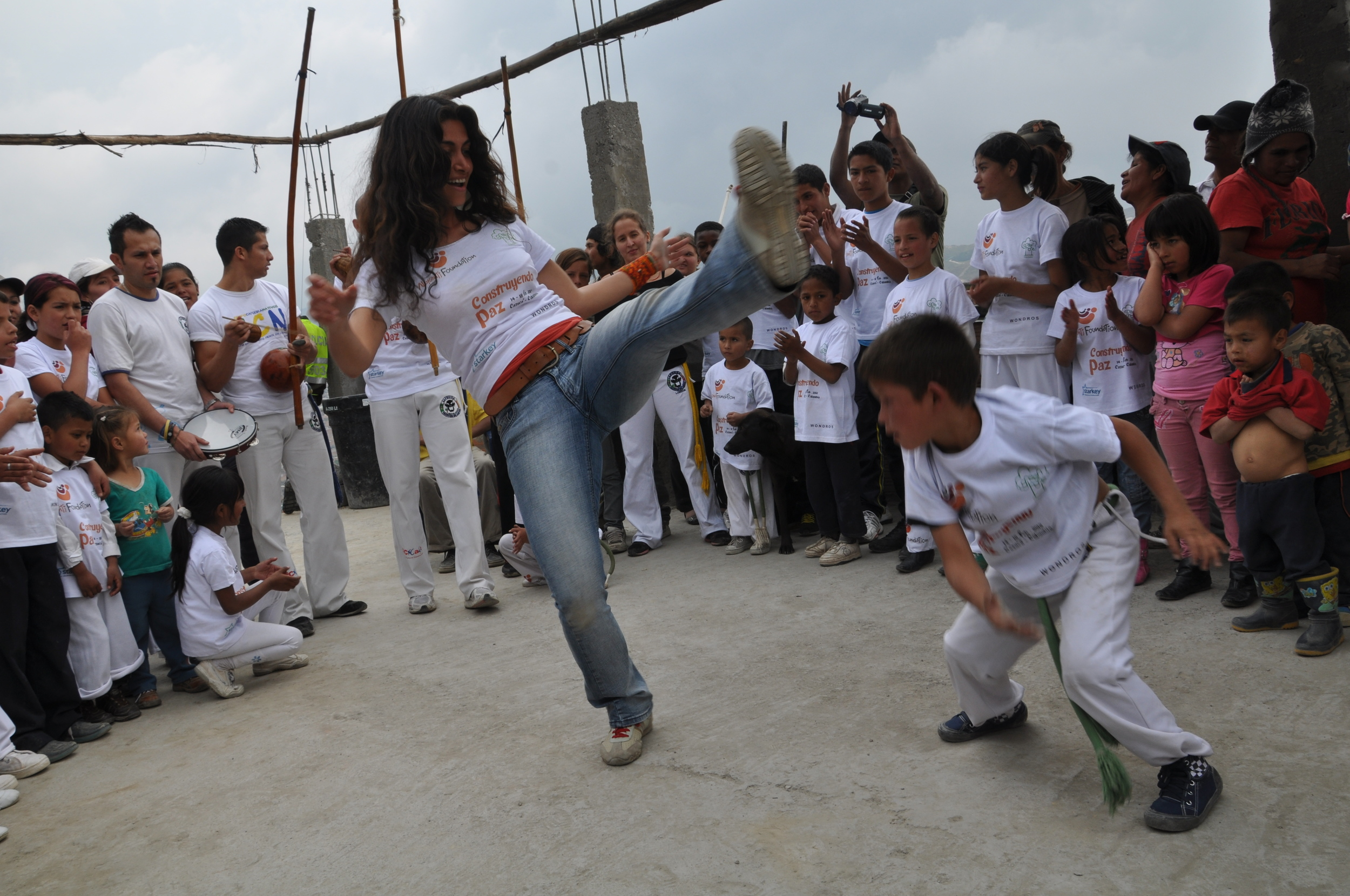 Niousha and a young participant from our Capoeira program Playing for Freedom in one of the first rodas in Cazucá, before the center was built.