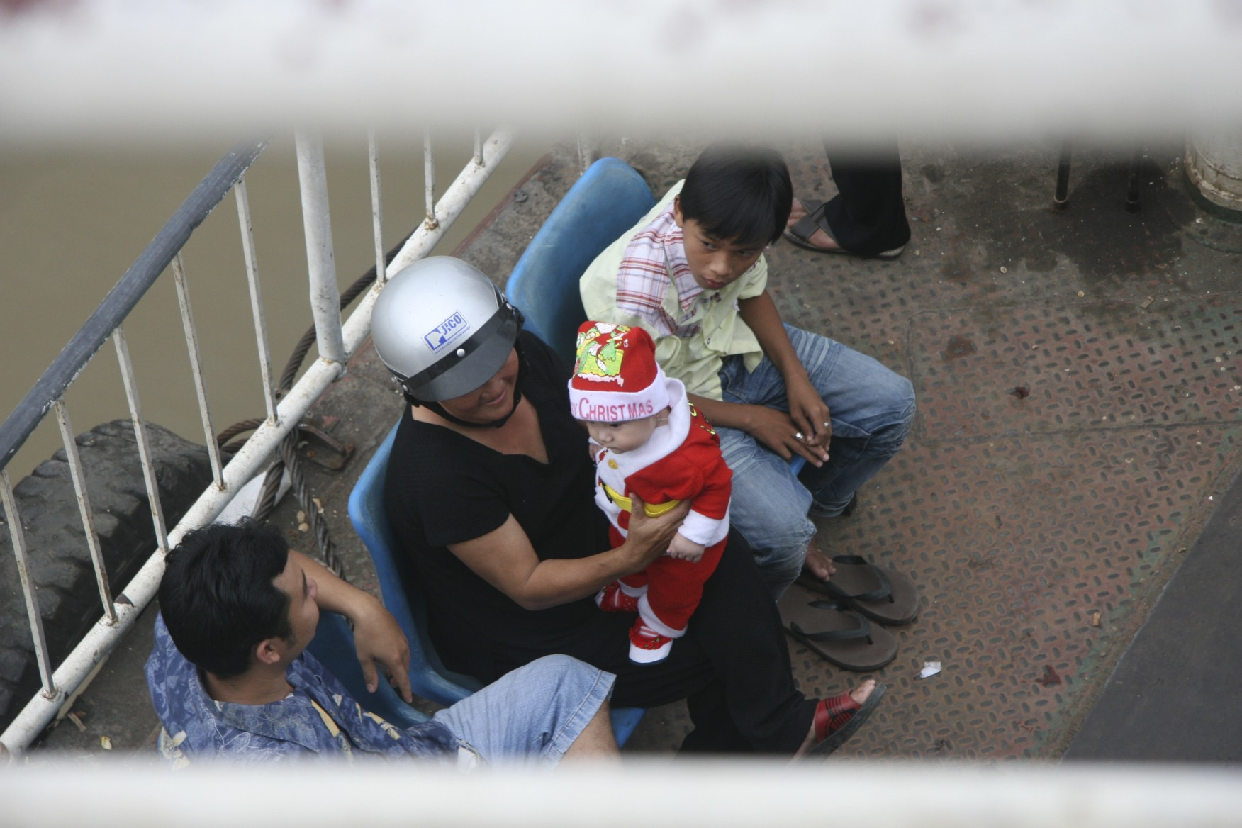 Vietnamese kid in a Santa suit on a ferry.