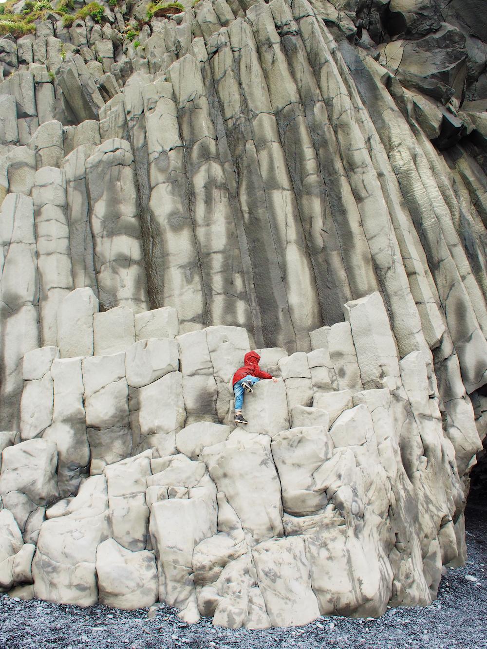 Hunter climbing the Reynisfjara basalt columns
