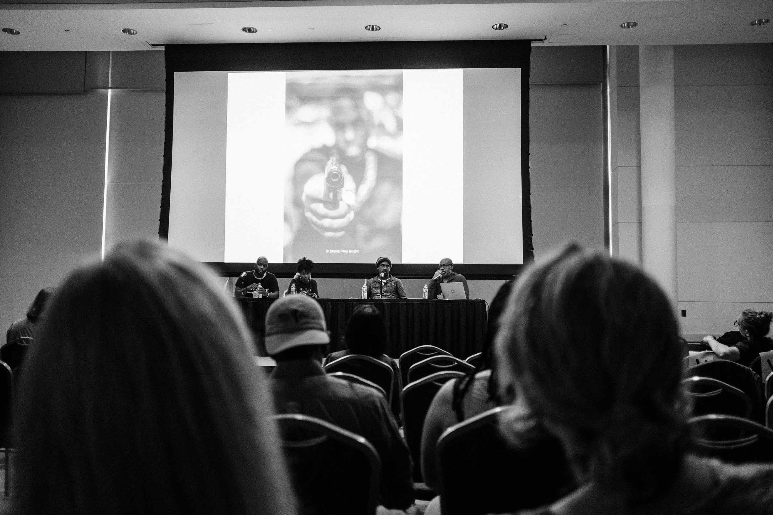 Ibarionex Perello moderates a panel on Mental Health - Behind and in front of the camera. Panelist included Ruddy Roye, Sheila Pree Bright and Michael McCoy.