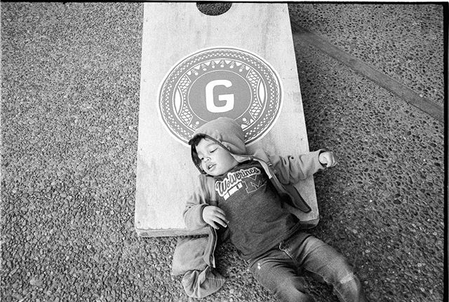 PRO TIP: Don't use your child as a bean bag when playing corn hole #madewithkodak #kodakcameraclub #documentyourdays #family #leicam6 #kodaktrix400