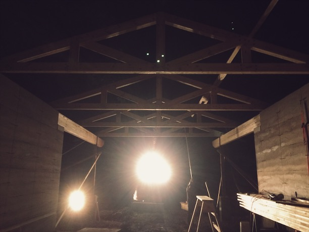 Site-built trusses being set with the excavator, at night no less.