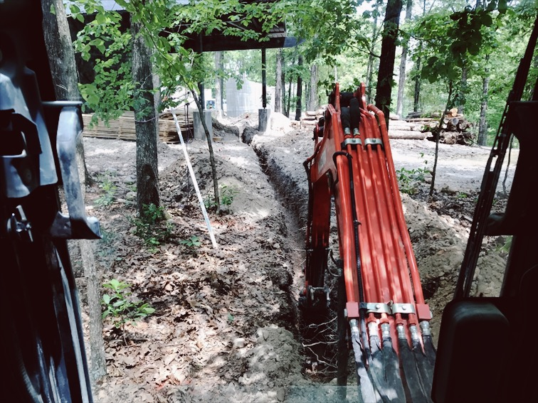 Me trenching for the sewer lines. Threading the needle through the garage columns.