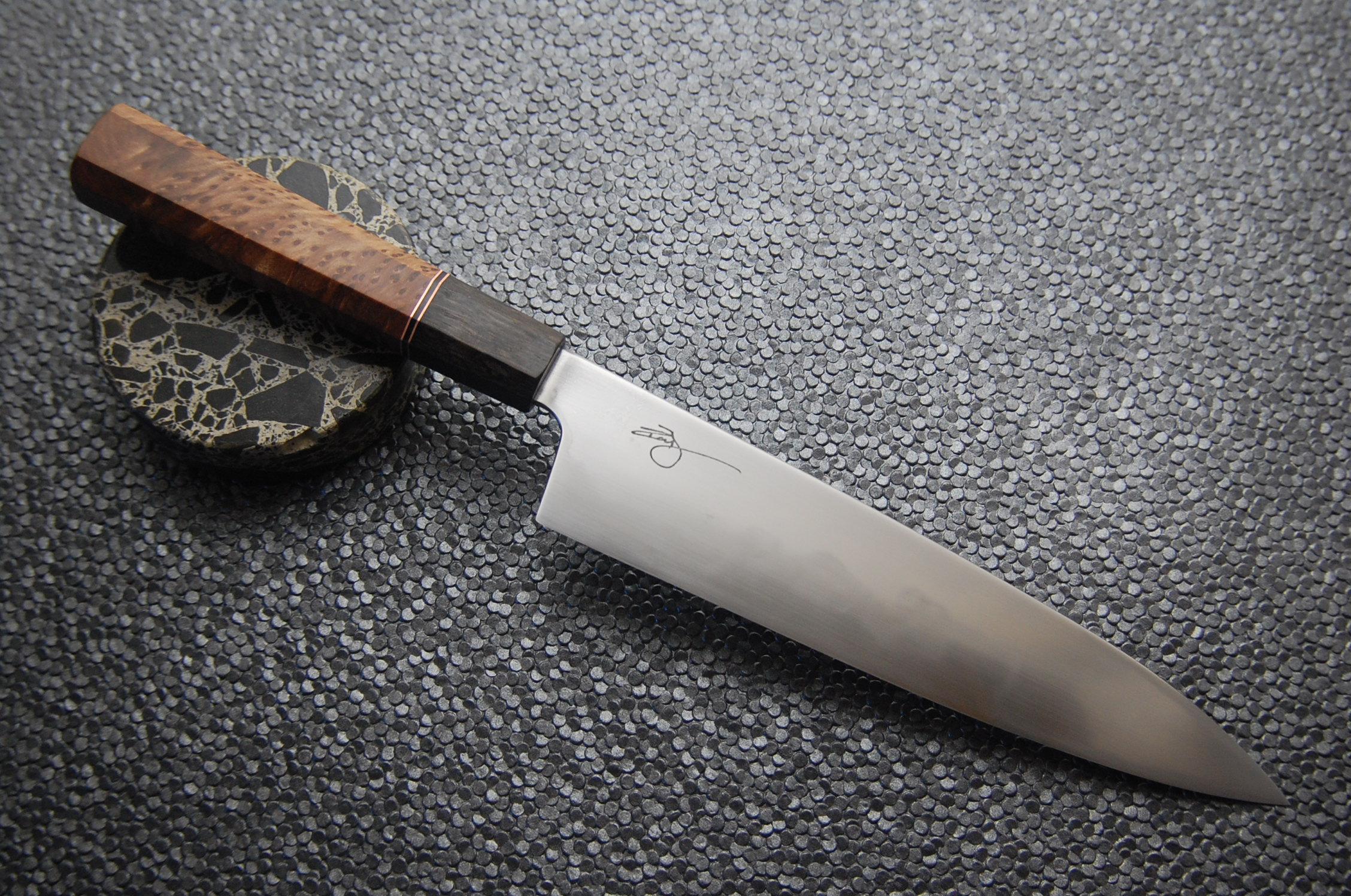 The steel is 1095 high carbon and the handle consists of black lacewood, copper, G10, and redwood burl.