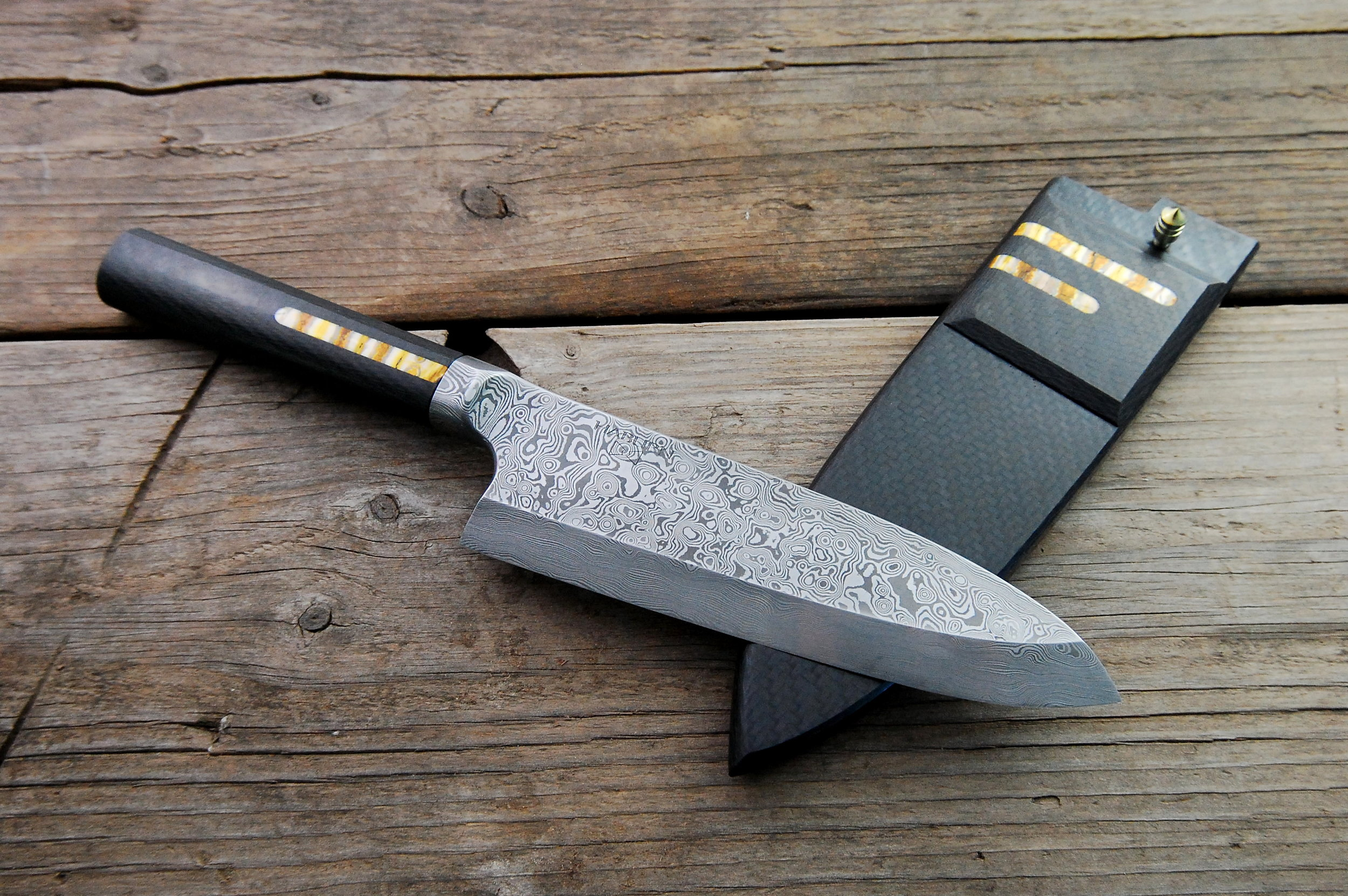 Custom Damascus Integral Deba handled in carbon fiber with yellow mammoth tooth inlays.