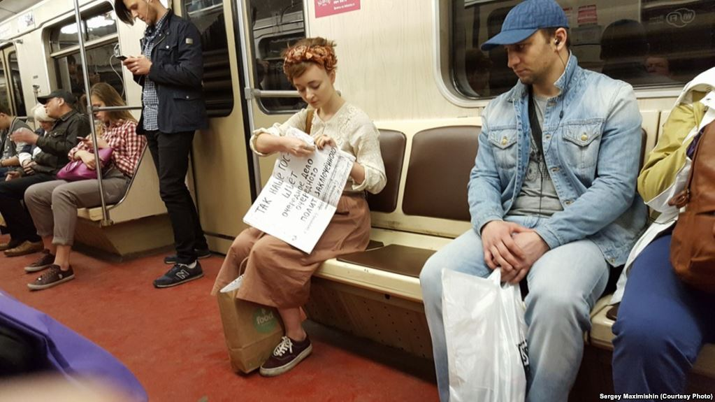Artist and poet Daria Serenko shows one of her poems on the Moscow metro