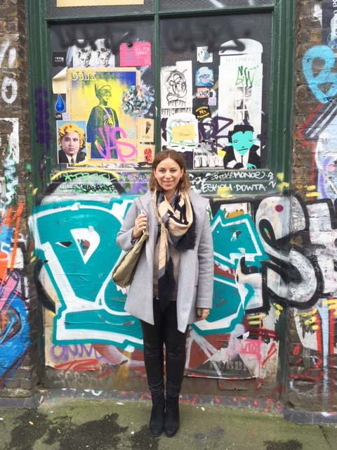 Casually in front of a graffitied wall in Shoreditch.