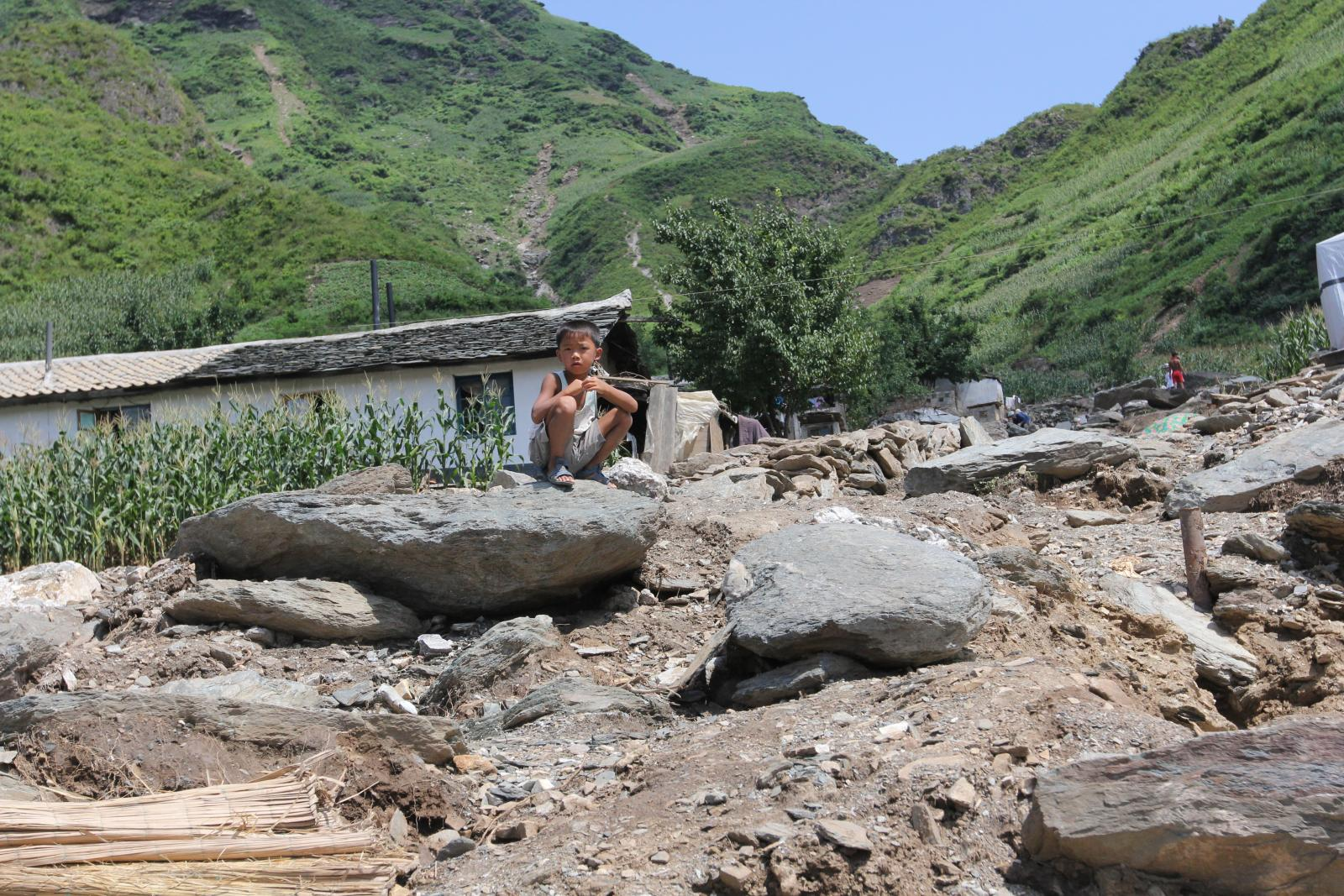 SONGCHON, North Korea _ A boy sits atop rubble left when flooding triggered a landslide that destroyed his village in Anju County, North Korea, in the summer of 2012. Photo by Jean H. Lee. All Rights Reserved.