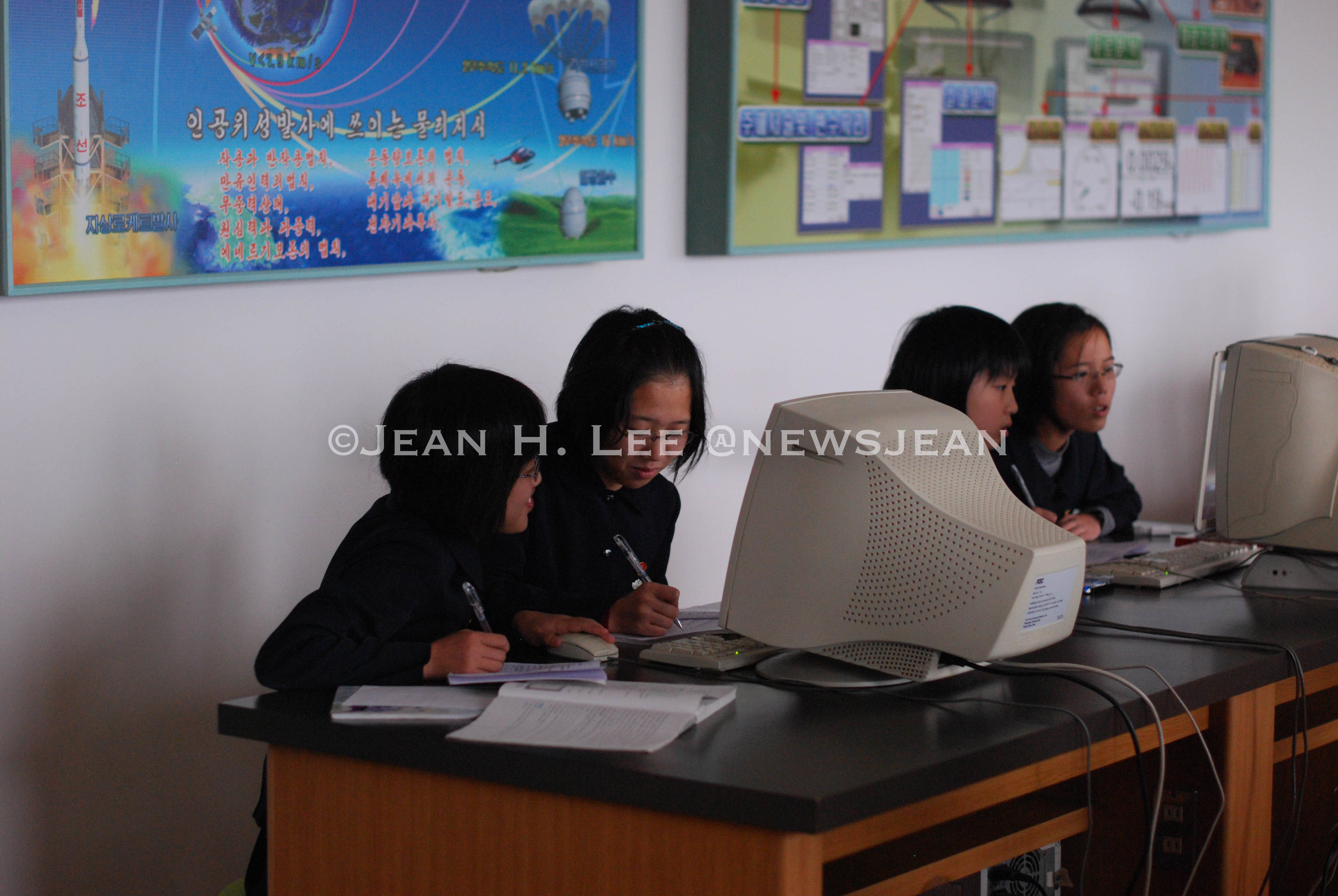 PYONGYANG, North Korea -- Middle school students work on a computer in front of a poster of North Korea's rockets and satellites behind them in this photo taken in Pyongyang, North Korea, on Oct. 24, 2011. (Photo credit: Jean H. Lee)