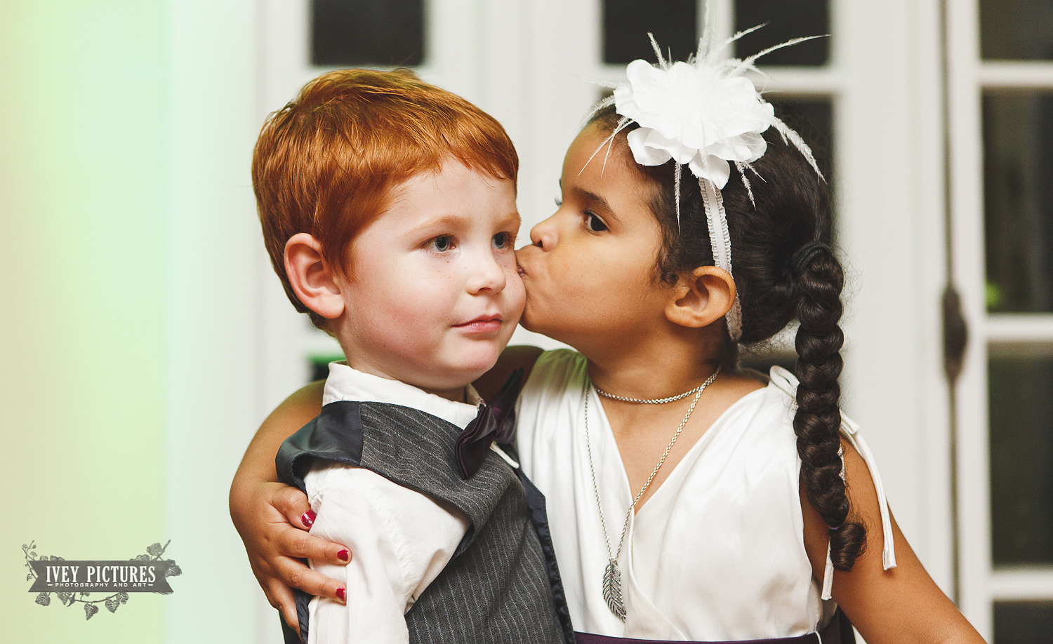 ring bearer and flower girl kissing