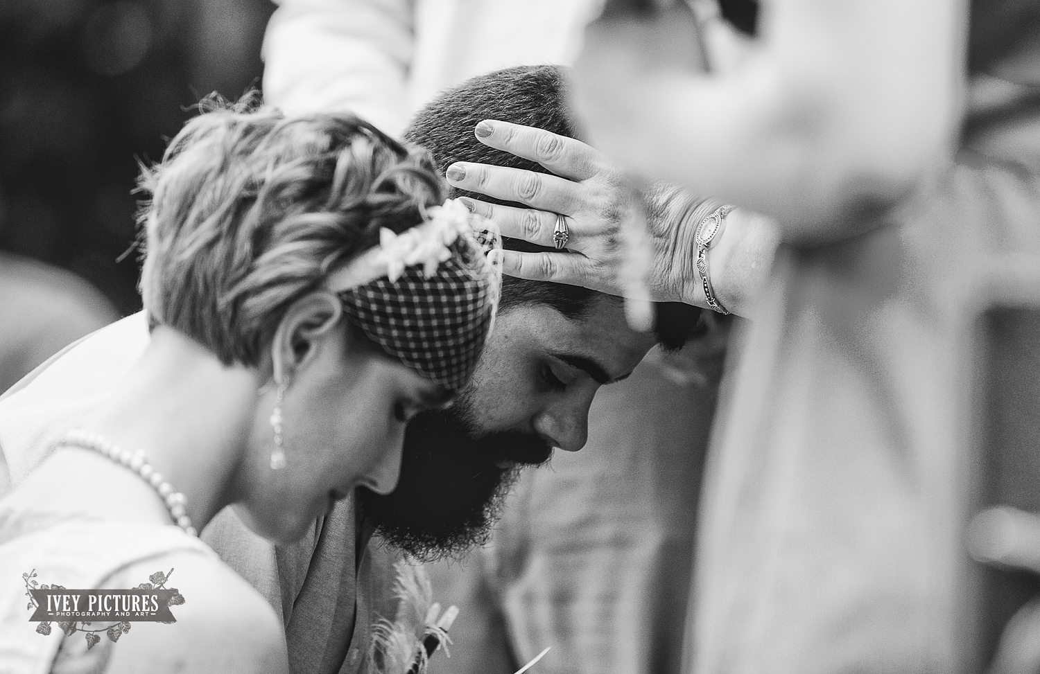 groom receiving blessing during wedding ceremony