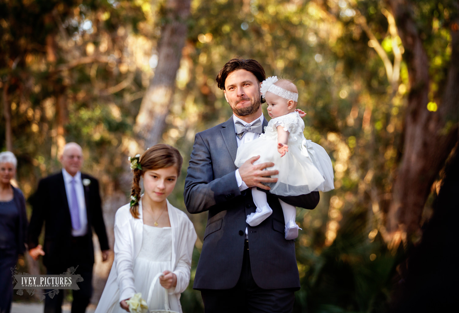 groom walking down isle with children