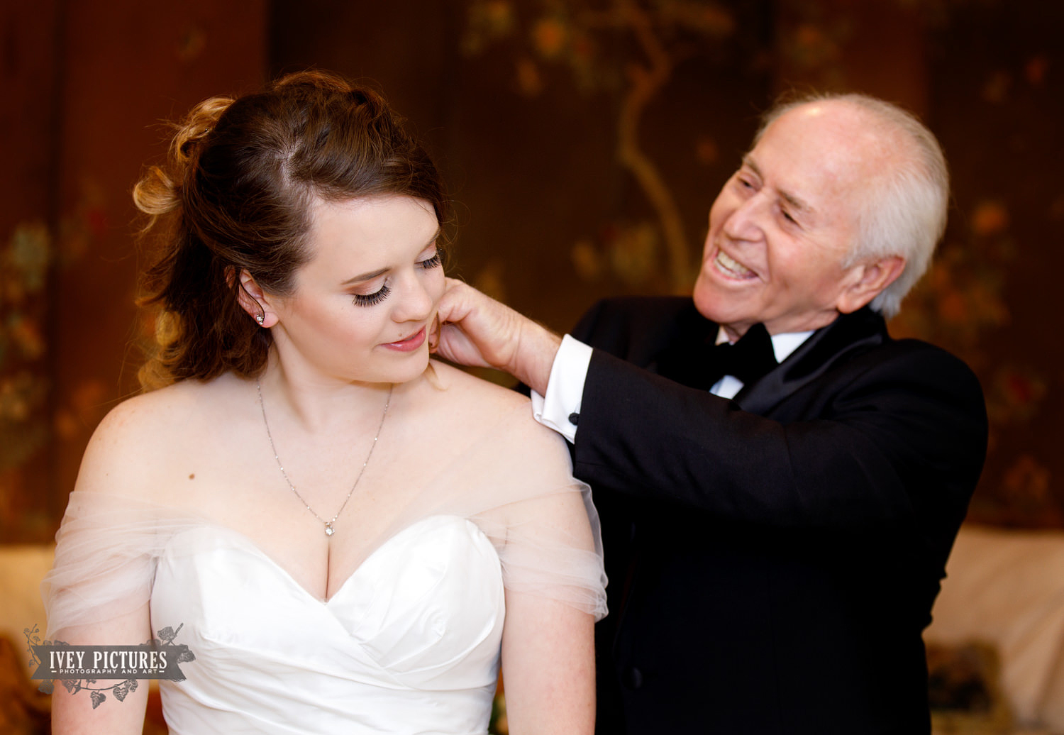 grandfather putting necklace on bride