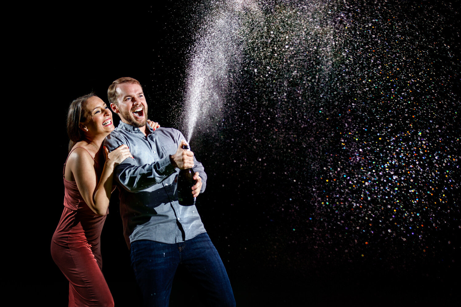 spraying champagne in engagement photos