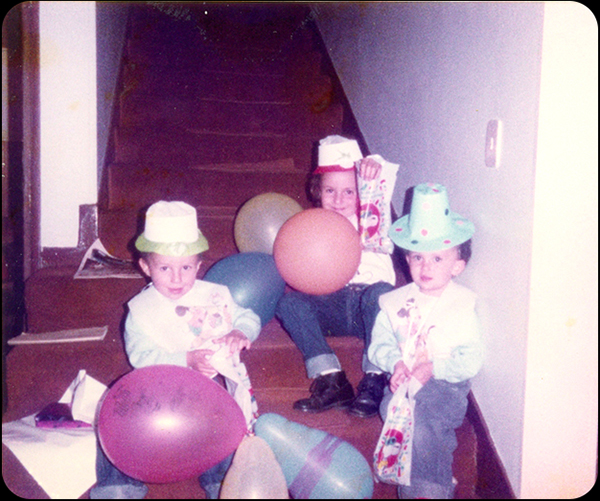 """Madeleine Garcia   """"Adjunto una fotito de mi cumple (soy la que levanta la bolsa muy orgullosa!)... no séde que año 198?... en casa de mi tío Luisito, estoy con mis hermanos con un babero de Mickey Mouse y con nuestra bolsita de Snoopy llena de caramelos... tiempo aquellos donde una bolsa de caramelos era el mejor de los regalos. Ahora que si el regalo no es un videojuego o la Nintendo, XBOX,etc...no es un buen regalo! Que viva el JAPIVERDI!!!"""""""