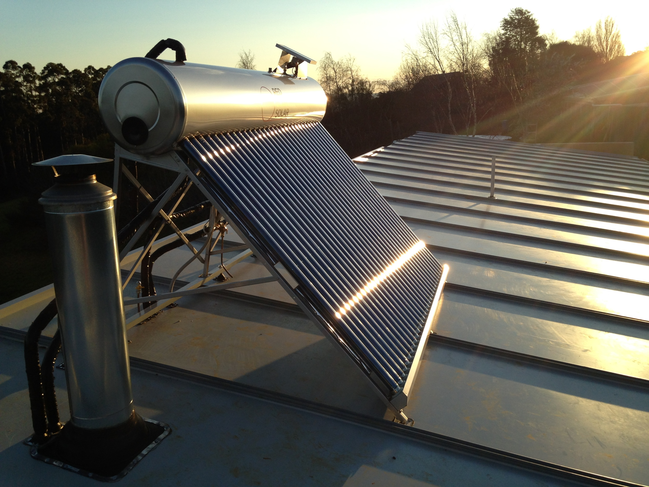 Wood fire hosted solar hot water
