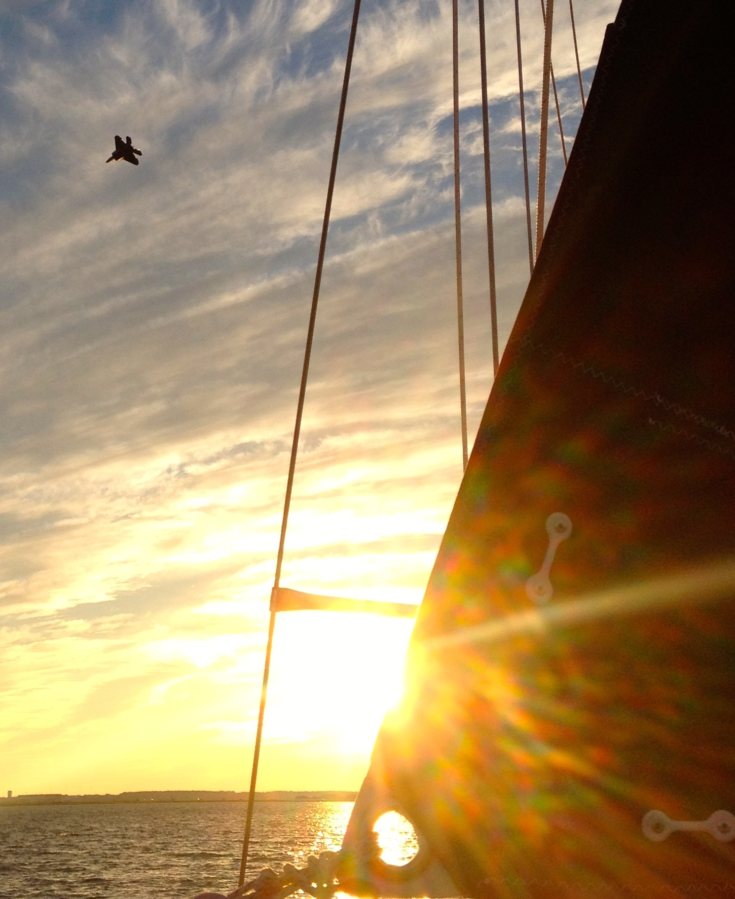 The trailing edge of Peregrinus' new mainsail and a screaming F22 above. 4:24PM, 18 November 2014, iPhone 4S.